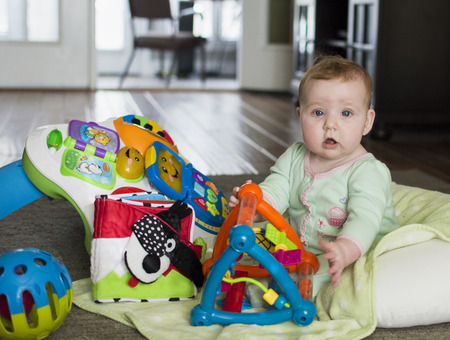 rosy cheeked: Baby sitting on floor with colorful toys looking at viewer Stock Photo