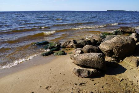 Big stones on the beach of Rybinsk reservoir. Summer seascape with ripple waters and bowlders.Yaroslavl region, Russia 写真素材