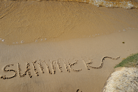 Summer written on the sea sand. Erased letters. Natural sandy background with beach and transparent pure wave. Place for text