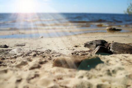 Summer seascape with sunbeam. Big stones on a sandy beach. Blurred sea on the horizon. Dreamy landscape. Rybinsk reservoir, Yaroslavl region, Russia