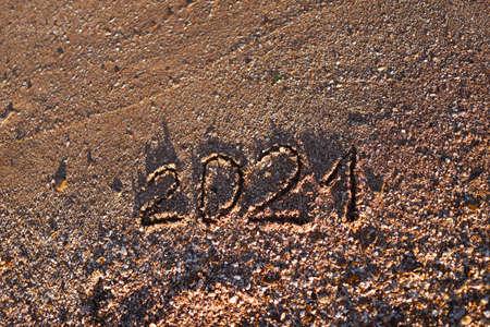 2021 written on sea sand. Sandy textured background.