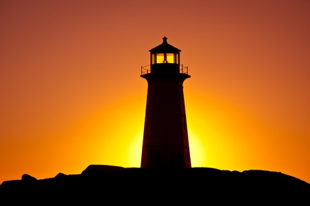 Nova Scotia: Peggys Cove lighthouse silhouetted against an orange-coloured sky at sunset, Nova Scotia.