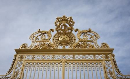 Ornate gold painted wrought iron gates at the entrance to the Chateau de Versailles.