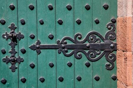 Ornate wrought iron hinge on a heavily iron-studded castle door. Banco de Imagens