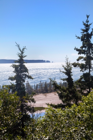 View across the Bay of Fundy in  Nova Scotia to Cape Split under bright blue summer sky  photo