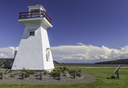Five Islands Lighthouse on Bay of Fundy coast of Nova Scotia under a blue summer sky with white clouds  Stock Photo