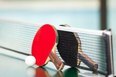 ping pong: Two table tennis or rackets and balls on a green table with net Stock Photo
