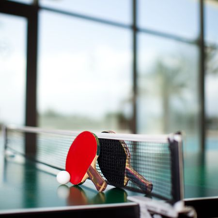 Two table tennis or ping pong rackets and ball on a green table with net Stock Photo