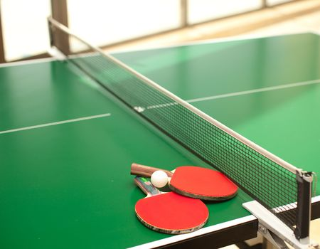 table tennis: Two table tennis or rackets and balls on a green table with net Stock Photo