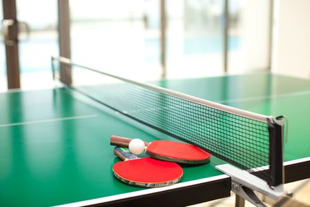 leisure centre: Two table tennis or rackets and balls on a green table with net Stock Photo