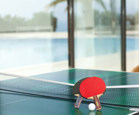 Two table tennis or rackets and balls on a green table with net,  swimming pool and sea in the background
