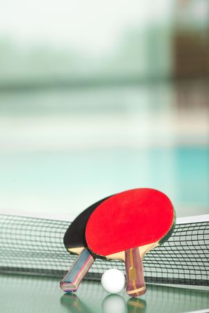 Two table tennis or ping pong rackets and ball on a green table with net, swimmig pool in the background