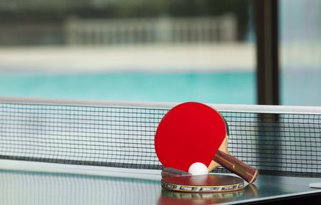 Two table tennis or rackets and ball on a green table with net, swimming pool in the background