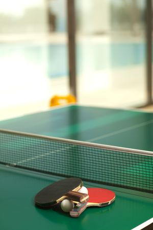 Two table tennis or rackets and balls on a green table with net, swimming pool in the background