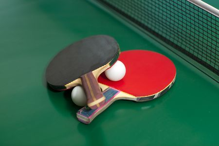 Two table tennis or rackets and balls on a green table with net photo