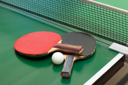 Two table tennis or rackets and ball on a green table with net