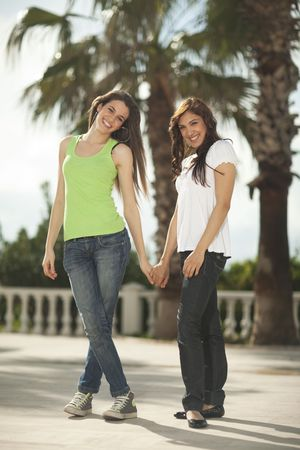 Two beautiful young women holding hands and having fun under palm trees smiling to the camera Stock Photo - 6347143