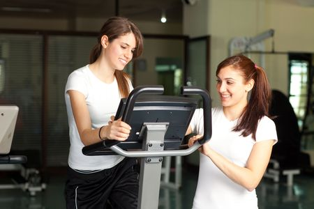 Two happy young women on a bike in the gym smiling