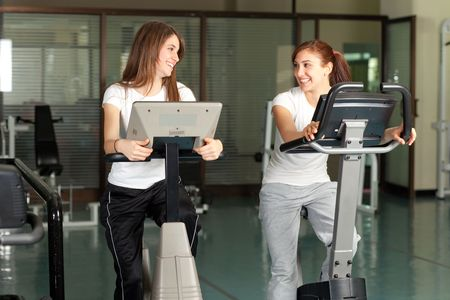 Two happy young women on a bike in the gym smiling to eachother Stock Photo - 6347227