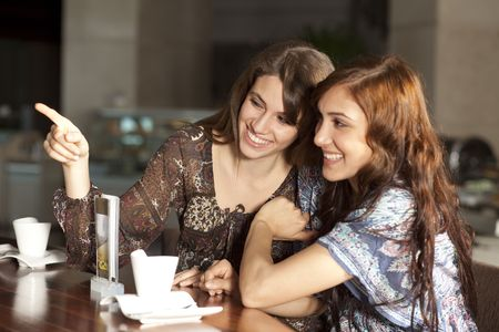 Two beautiful young women with great teeth enjoying their lunch break, sitting at a bar, drinking coffee, smiling. Selective focus on back woman.