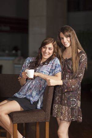 Two beautiful young women with great teeth enjoying their lunch break, sitting at a bar, drinking coffee, smiling Stock Photo - 6378255