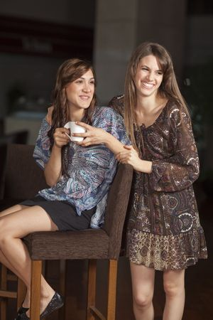 Two beautiful young women with great teeth enjoying their lunch break, sitting at a bar, drinking coffee, smiling Stock Photo - 6378257