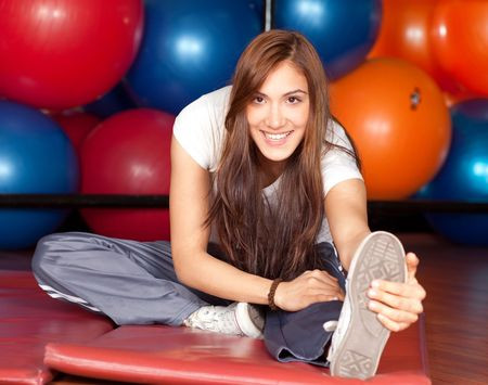 Happy young women stretching in the gym smiling to the camera