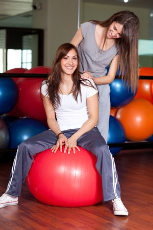 tracksuit: Two happy young women sitting on a red ball in the gym smiling to the camera Stock Photo
