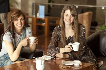Two beautiful young women with great teeth enjoying their lunch break, drinking coffee, smiling to the camera Stock Photo - 6378262
