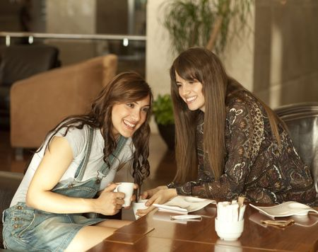 Two beautiful young women with great teeth enjoying their lunch break, drinking coffee, sharing a secret.