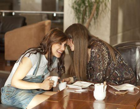 Two beautiful young women enjoying their lunch break, drinking coffee, sharing a secret. photo