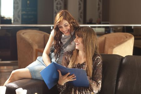 menue: Two beautiful young women with great smile enjoying their lunch break, drinking coffee, reading the menue. Stock Photo