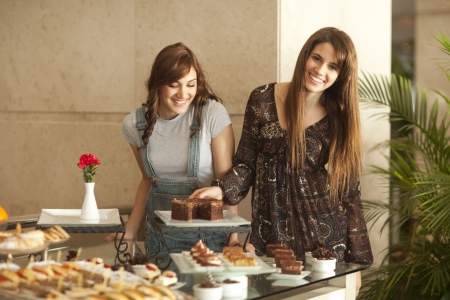 Two beautiful young women with great teeth enjoying a dessert buffet, smiling to the camera, palm tree in the background.