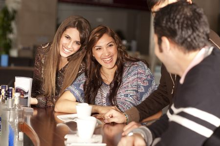 Two beautiful young women with great teeth enjoying their lunch break, sitting at a bar, flirting, drinking coffee, smiling