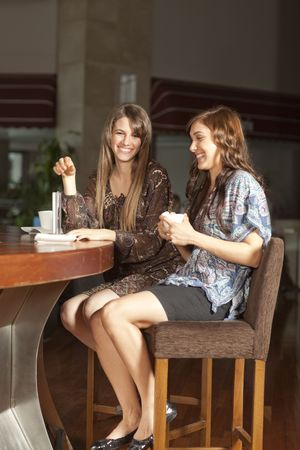 socializing: Two beautiful young women with great teeth enjoying their lunch break, sitting at a bar, drinking coffee, smiling. Selective focus on back woman.