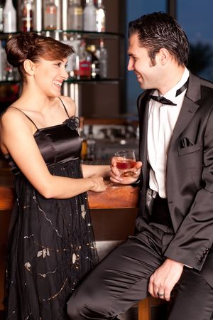Young couple at a bar, men in black tuxedo holding whisky in his hand, woman with hairstyle in black dress smiling Stock Photo - 6428685