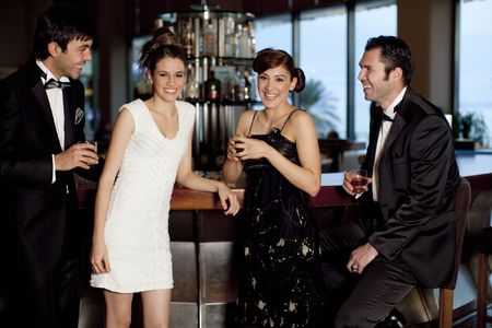 Two young couples at a bar, men in black tuxedo, drinking whisky, flirting, smiling, palm tree in the background Stock Photo