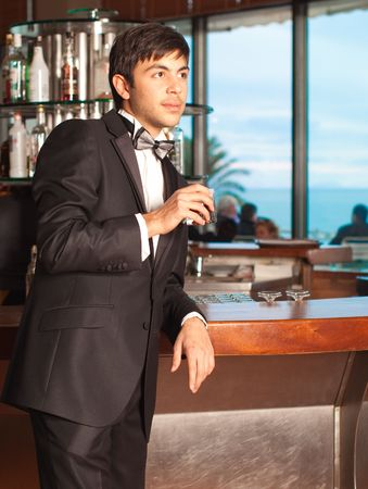 Handsome young man in a black tuxedo at a round bar holding whisky in his hand; palm tree and sea in background Stock Photo