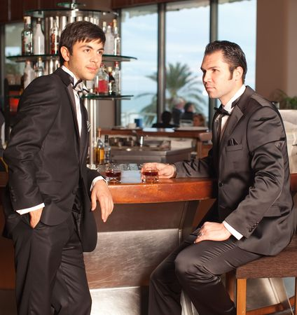 Two handsome young men in a black tuxedo at a round bar drinking whisky, palm tree in the background