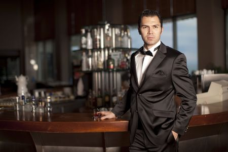 Handsome young man in a black tuxedo at a round bar holding whisky in his hand; shallow depth of field, focus on face.
