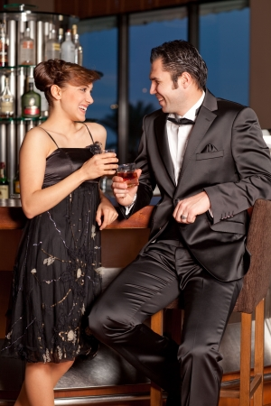 Young couple at a bar, men in black tuxedo holding whisky in his hand, woman with hairstyle in black dress smiling Stock Photo