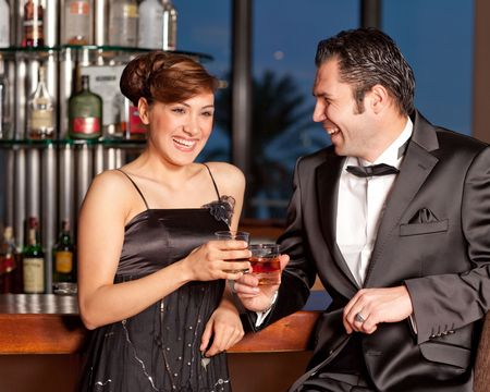 Young couple at a bar, men in black tuxedo holding whisky in his hand, woman with hairstyle in black dress smiling Stock Photo - 6378305