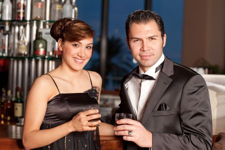 Young couple at a bar, men in black tuxedo holding whisky in his hand, woman with hairstyle in black dress smiling to the camera Stock Photo - 6378283