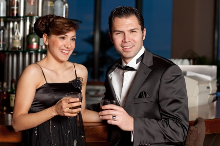 Young couple at a bar, men in black tuxedo holding whisky in his hand, woman with hairstyle in black dress smiling to the camera Stock Photo