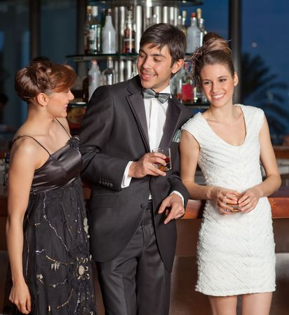 Three young people at a bar, men in black tuxedo holding whisky in his hand, women with hairstyle in black and white dresses smiling, palm tree in the background Stock Photo - 6378292
