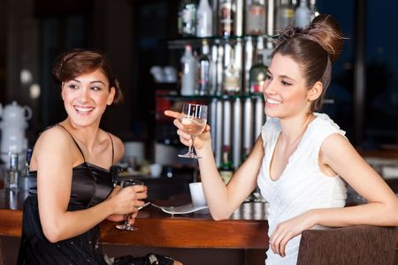 Two beautiful young women with great smile and hairstyle sitting at a bar, drinking water. Stock Photo