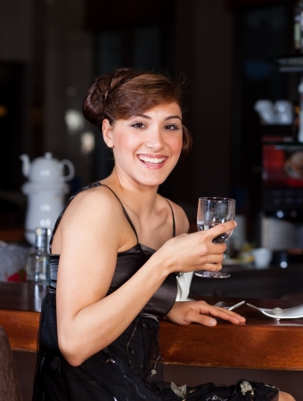 Beautiful young women with great smile and hairstyle sitting at a bar, drinking water. photo
