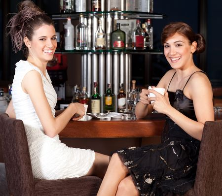Two beautiful young women with great smile and hairstyle sitting at a bar, drinking coffee, smiling to the camera photo