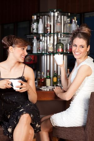 Two beautiful young women with great smile and hairstyle sitting at a bar, drinking coffee. photo