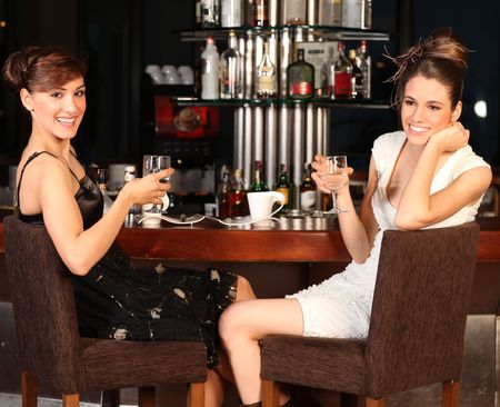 socializando: Dos hermosas mujeres j�venes con gran sonrisa y peinado, sentado en un bar, beber agua.
